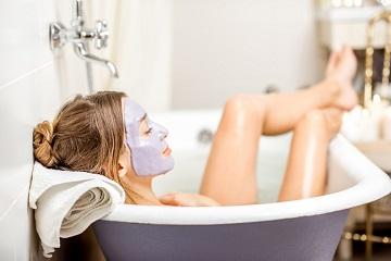 En kvinna i badkaret med en mask