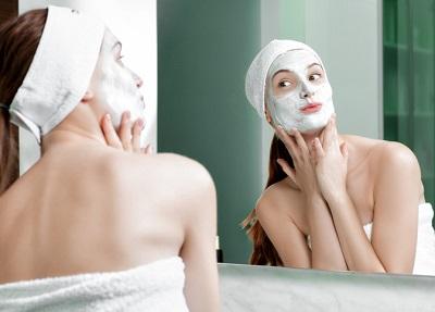 En tjej med ansiktsmask tittar sig i spegeln